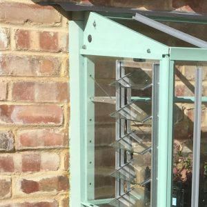 Close up of fixing mini greenhouse to a wall